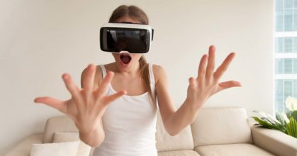 Surprised excited young girl wearing VR glasses looking at hands
